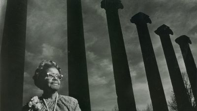 In a black and white photo, Lucille Bluford stands in front of The Columns