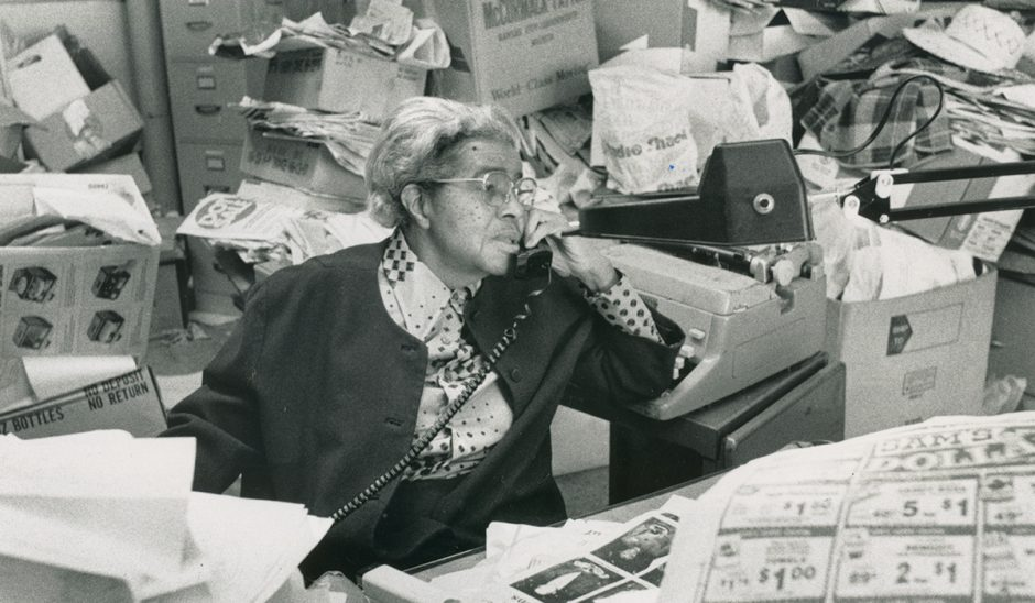 Lucille Bluford sits at her desk speaking on the phone.