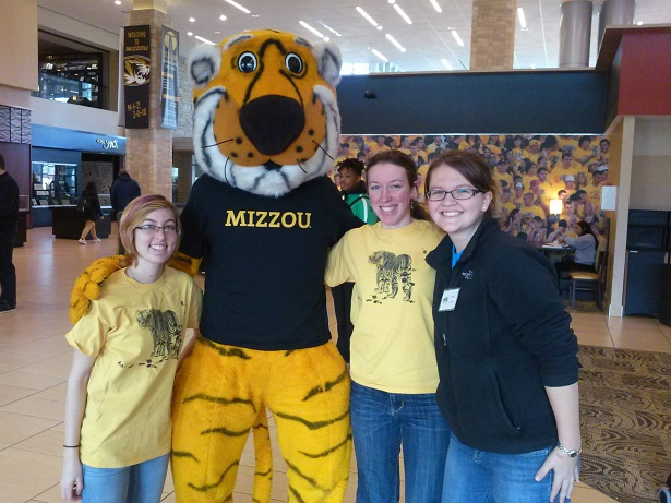 Three students stand with their arms around each other and the Mizzou mascot, Truman the Tiger