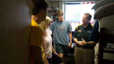 Chancellor Cartwright standing in a student's room and talking with a freshman student and his family.