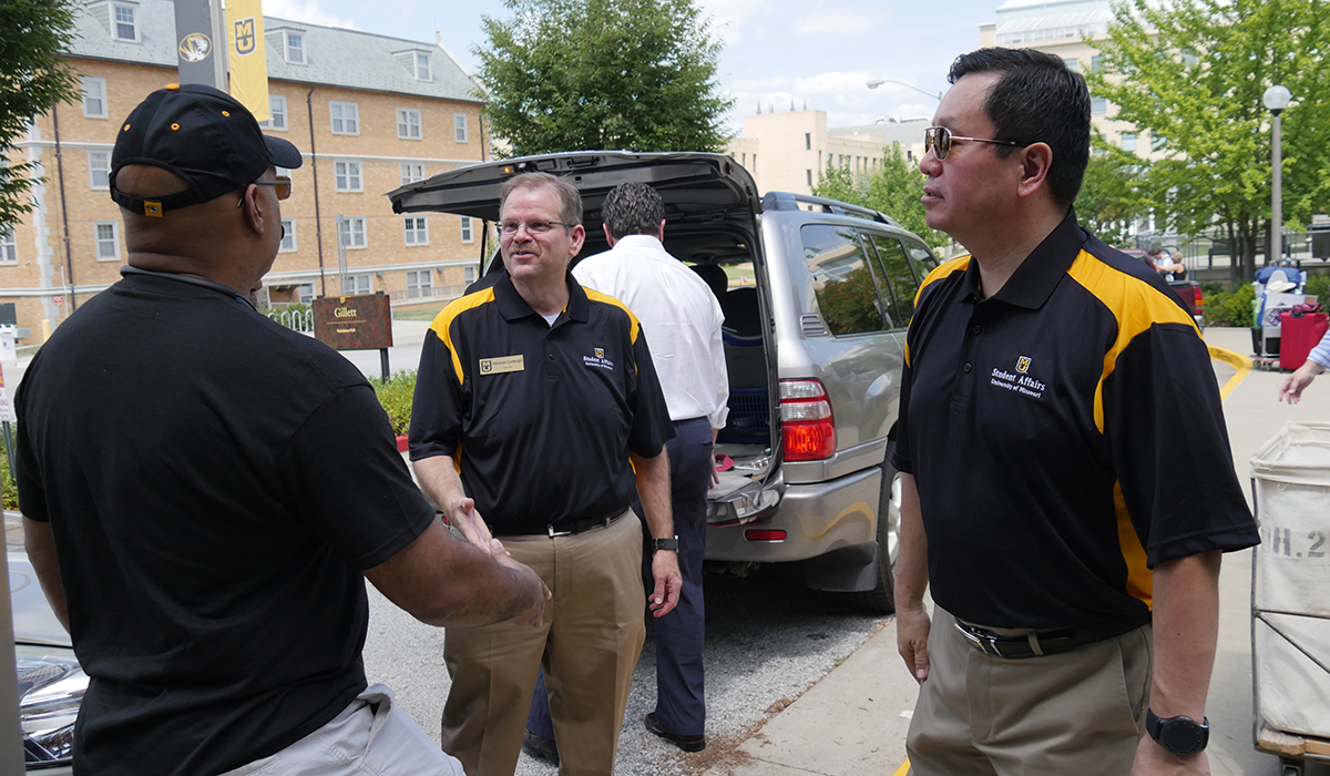 Chancellor Alexander Cartwright shakes hands with a Mizzou parent during move-in day while President Choi looks on.