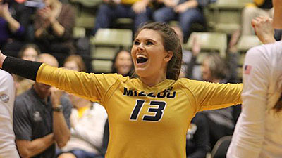 Alexa Ethridge, with arms outstretched celebrates a point in a volleyball match.