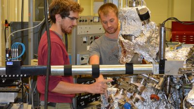 Fourth-year physics doctoral candidate Alessandro Mazza (left) works on an ultra-high vacuum called X3B2 with physics graduate student Alexander Daykin in Prof. Paul Miceli's lab.
