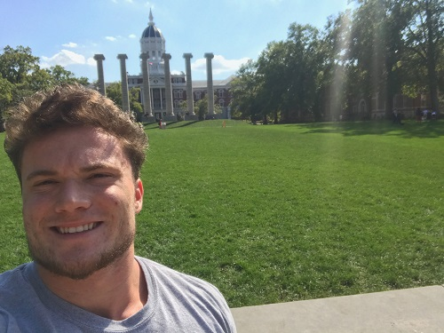 This is a picture of Adam Weaver in front of the Columns and Jesse Hall