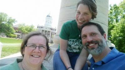 Picture of Ashleigh Redman as a child sitting at the Columns with her parents