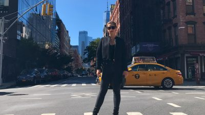 This is a picture of Mackenzie Mattix standing in a NYC intersection with the NYC skyline visible in the background