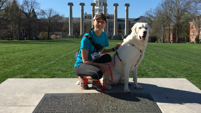 This is a picture of Megan Hicks and her dog in front of Jesse Hall and the Columns