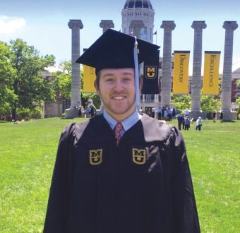 This is a picture of Ryan Platt in graduation regalia in front of Jesse Hall