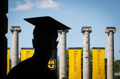 Photo of a graduate in front of the columns