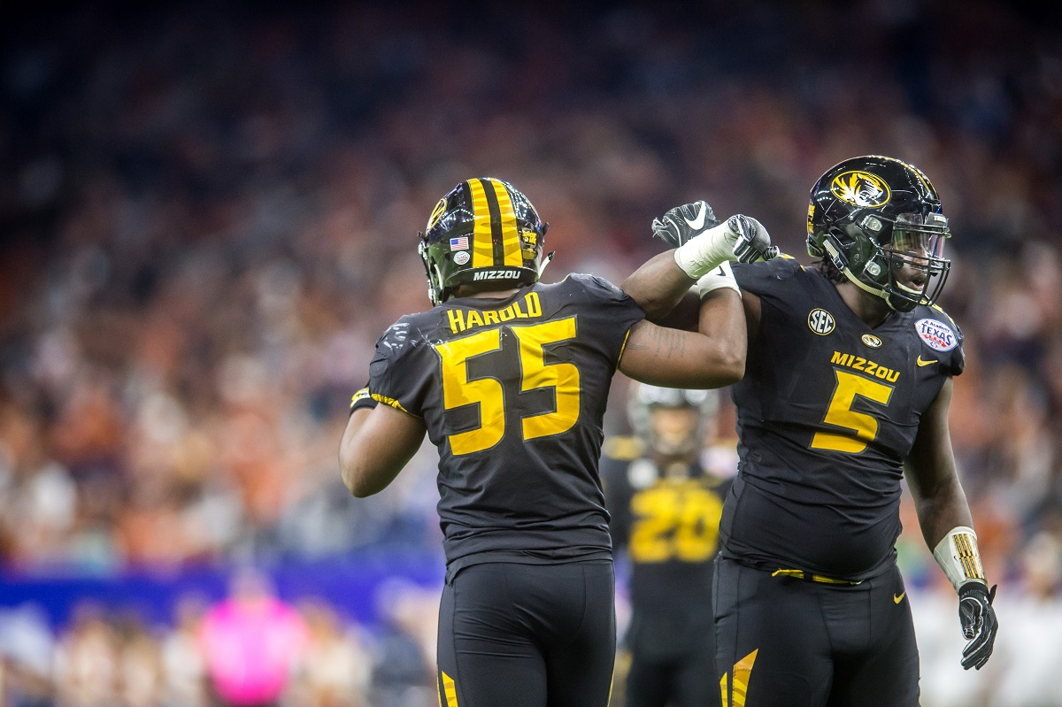 Missouri defensive linemen Jordan Harold (55) and defensive lineman Terry Beckner Jr. (5) celebrate a defensive stop.