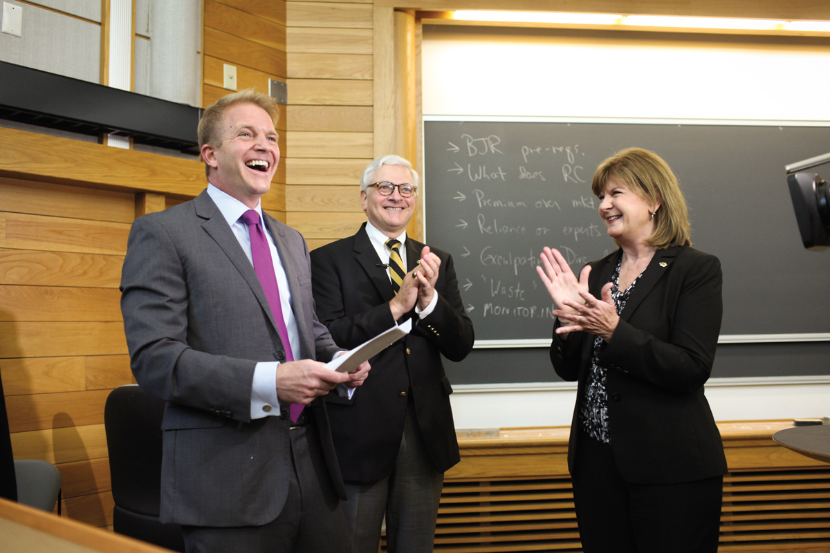 This is a picture of Thom Lambert laughing with former interim Chancellor Hank Foley and Commerce Bank Chairman and CEO Teresa Maledy cheering.
