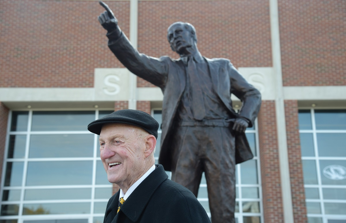 This is a picture of Norm Stewart smiling in front of the Norm Stewart Statue