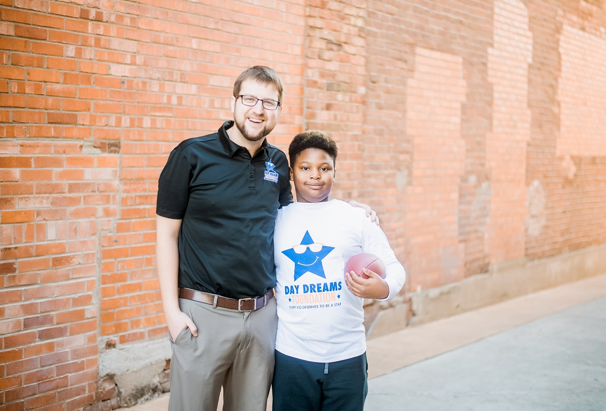 Picture of Joe Bradley with scholarship recipient Ja'Shaun posing with a football