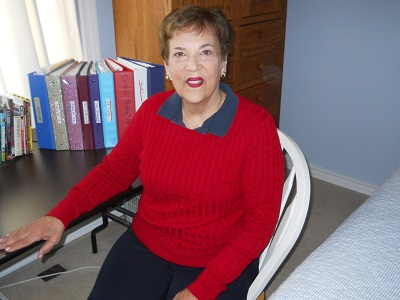Picture of Jackie Schroeder who graduated from Mizzou in 1961 sitting at a desk