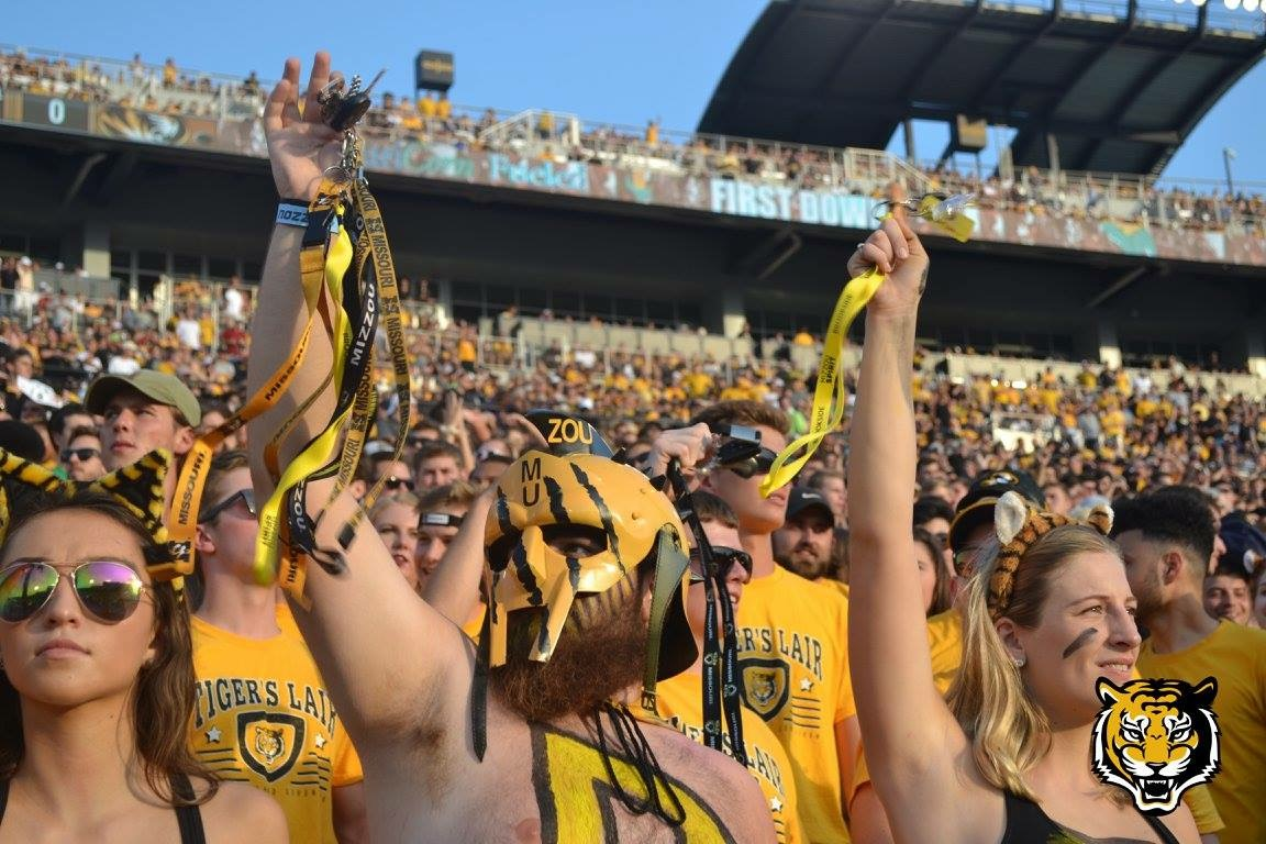 Picture of Truman Kinsey in the student section at Faurot, Kinsey is wearing a black and gold face mask and body paint and is dangling keys for the third down.