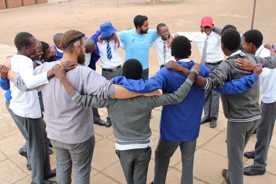 Mahir Khan in a circle of people in a Botswana village