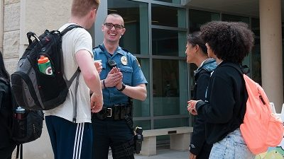 On a sunny afternoon in April, MUPD Officer Mitchel Smith talks with students, from left, Jared Holm, Emma Stetzenmeyer and Kennedi Keyes, as they wait outside the MU Student Center for a free lunch of hot dogs, hamburgers and potato chips. Interacting with students is a big part of Smith's job, which also involves developing campus partnerships and solving problems.