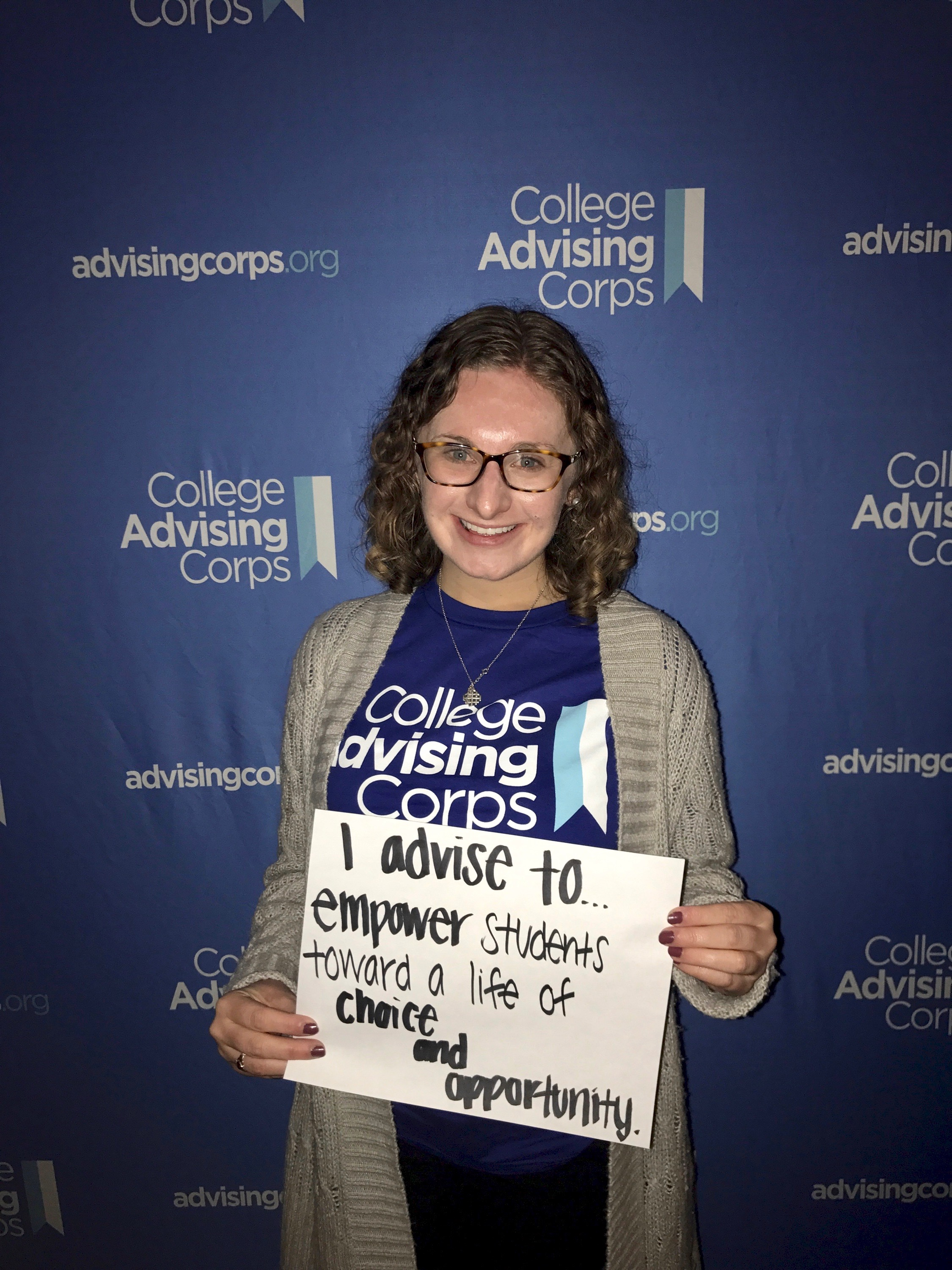 """Picture of Mary Kate Kelly with a sign about why she love being a college adviser. The sign reads """"I advise to empower others toward a life of choice and opportunity."""""""