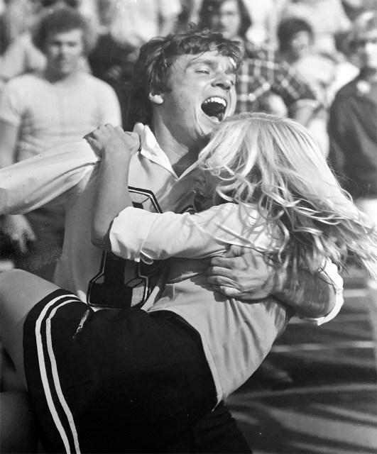 Picture of Jess Bushyhead in 1978 hugging a female cheerleader.