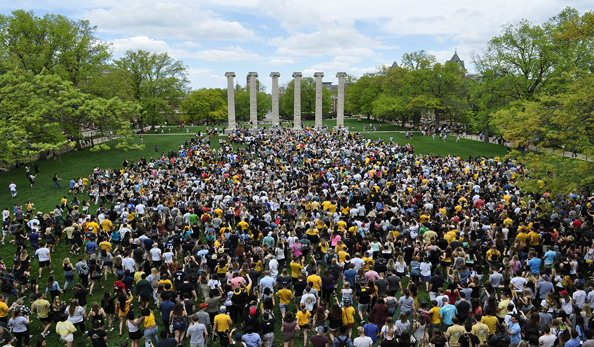Thousands of students walk toward the columns on their way into the world.