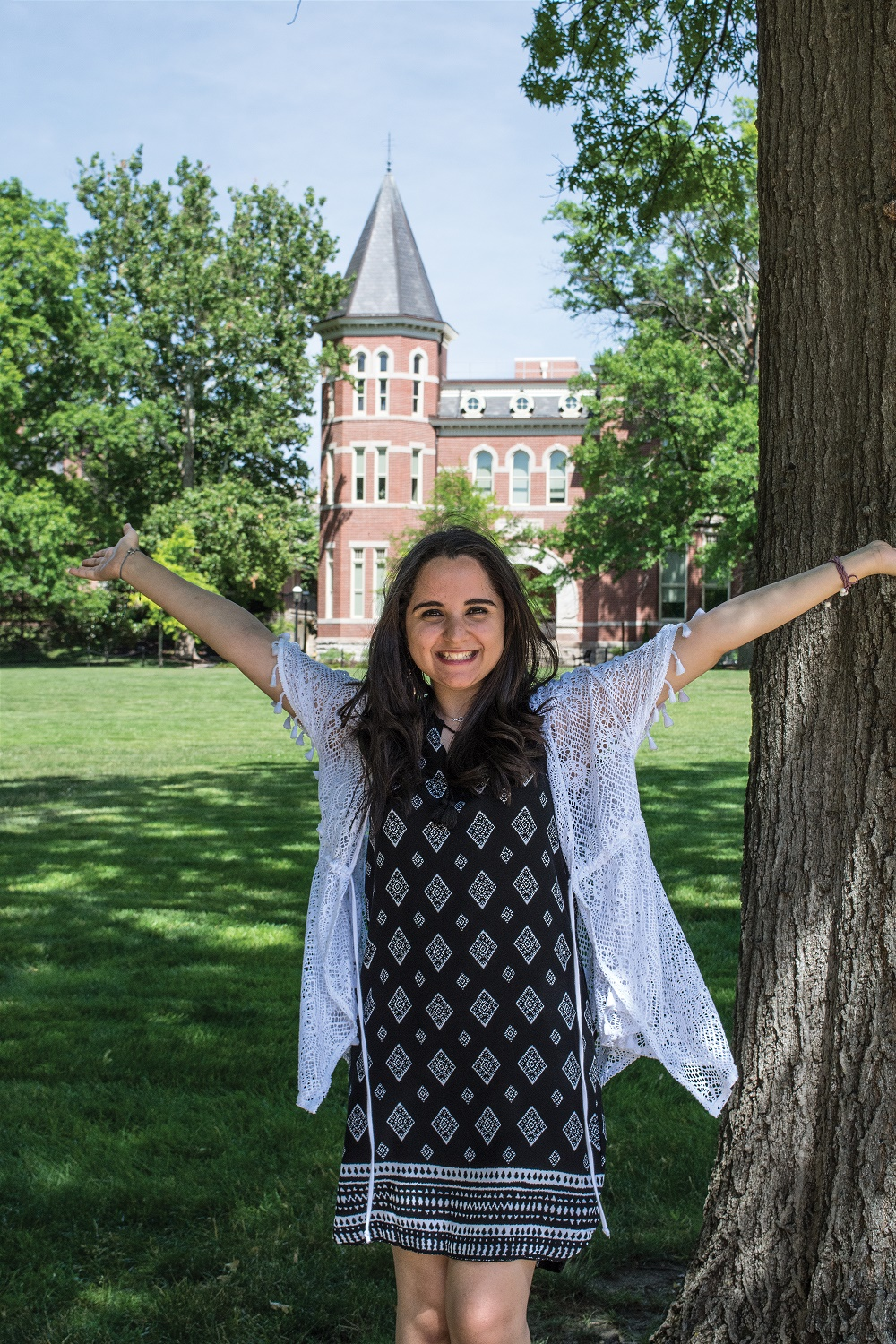 This is a picture of Dina Ahmed standing on the Quad with her arms outreached
