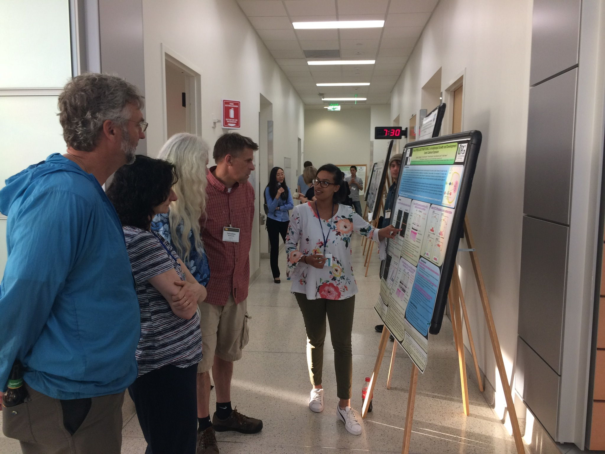 Lee-Ann explaining her poster to conference organzers at 2018 Plant Cell Dynamics meeting