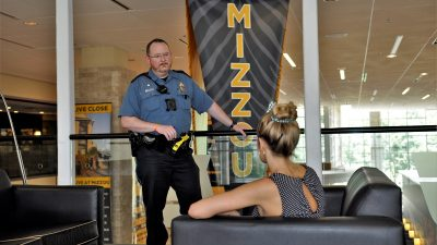 This is a picture of Officer Jacob Clifford talking to a student on the second floor of the MU student center
