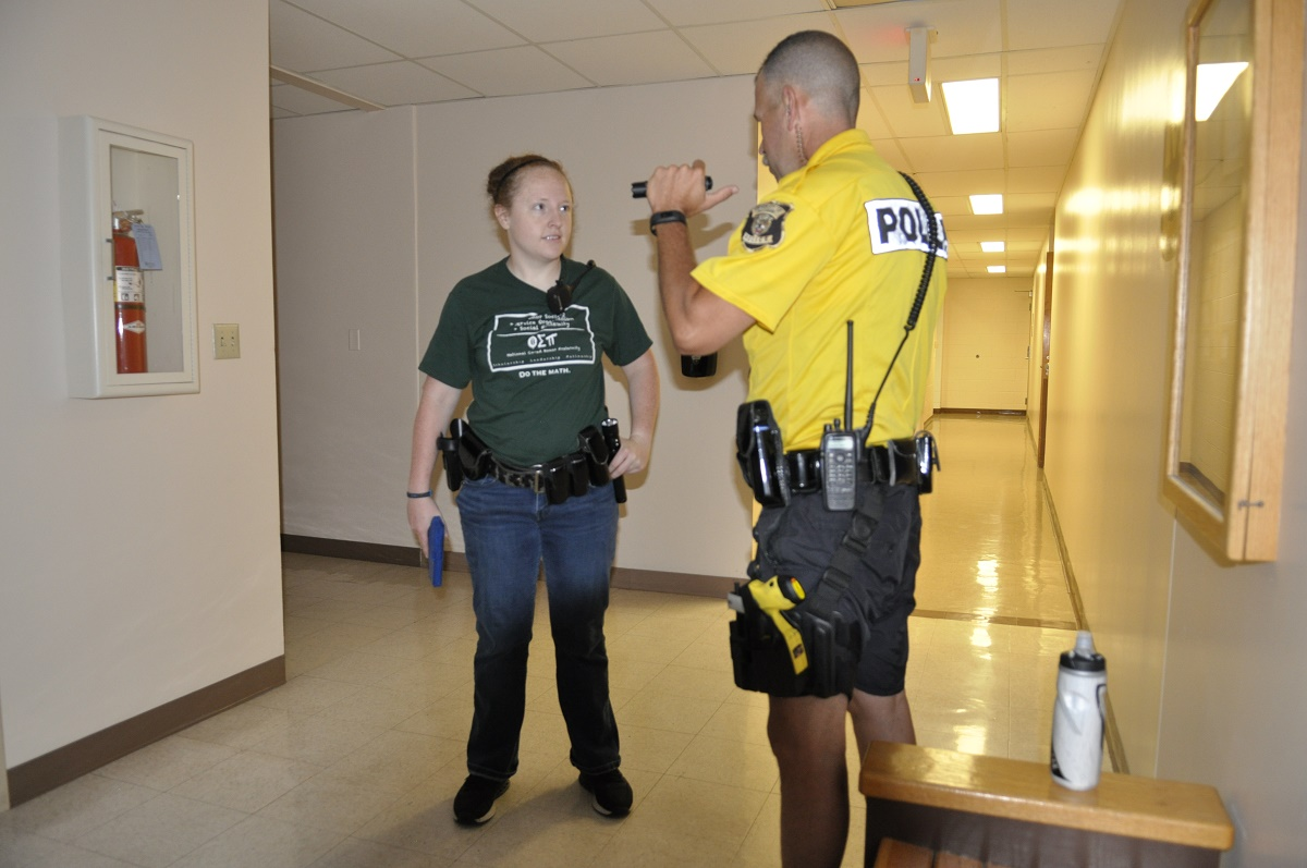 This is a picture of Officer Haley Eisenberg listens as Officer Brian Frey, a certified firearms instructor, gives her feedback following a training exercise that involved searching hallways and classrooms for a violent intruder.
