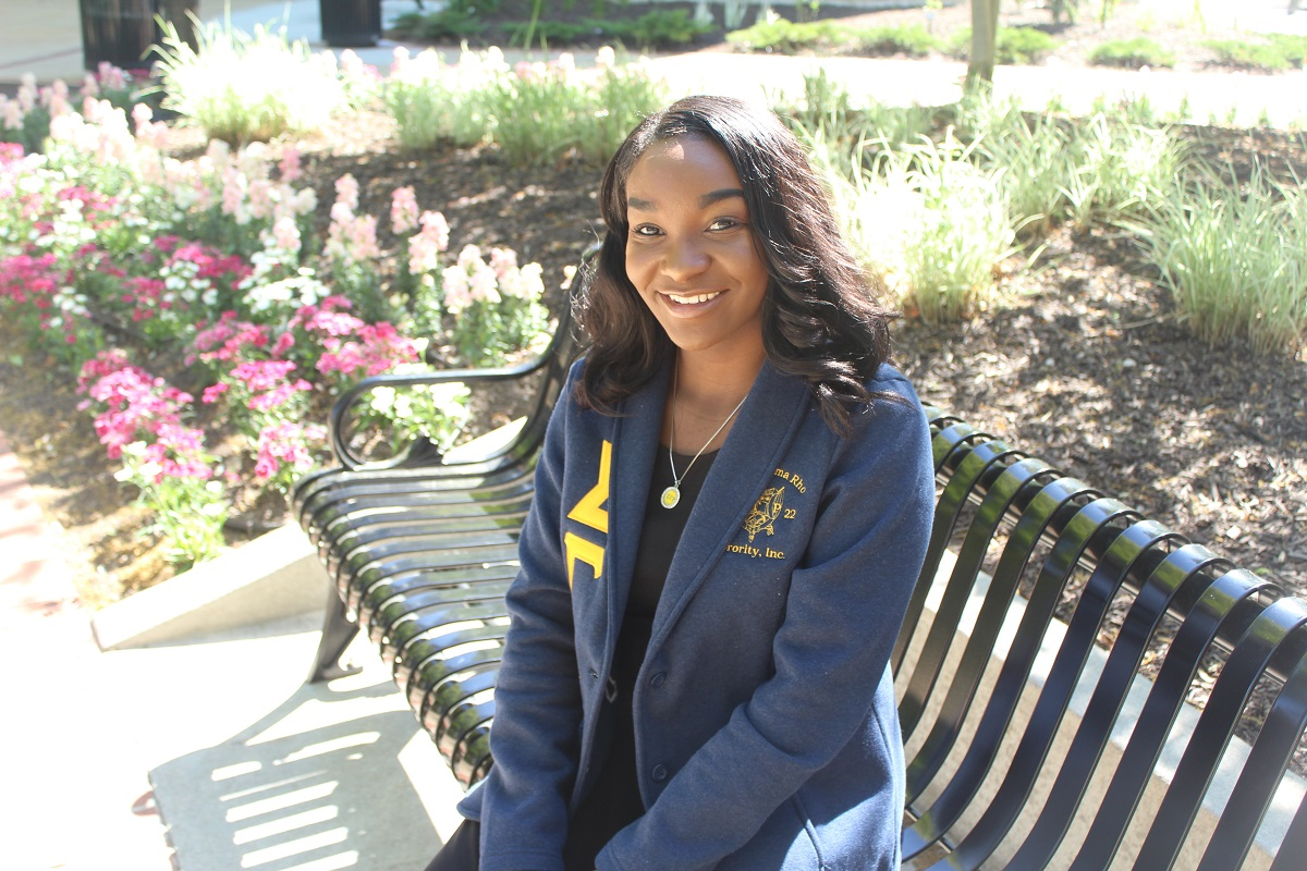 Picture of Tiera Montgomery sitting on the Quad.