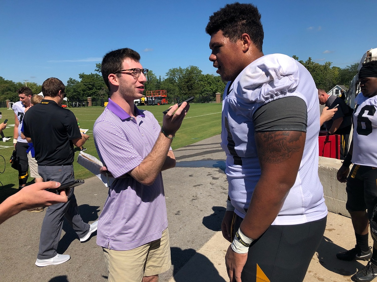 This is a picture of Alec Lewis interviewing Mizzou offensive lineman Kevin Pendleton during football practice