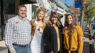 This is a picture of William Mowrer, Allie Mowrer, Melinda Mowrer, and Hannah Mower standing in downtown Columbia wearing Black and Gold Mizzou gear
