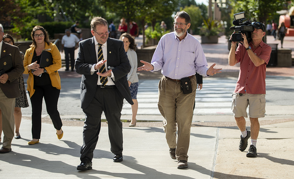 Chancellor Alexander Cartwright and George Smith share a laugh as they walk across campus