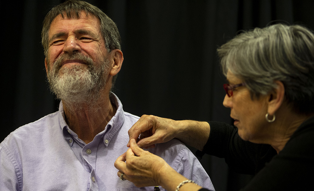 Dr. Marjorie Sable pins a pin to Dr. George Smith's shirt