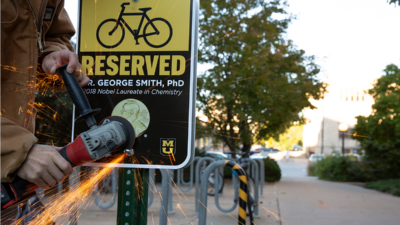 Campus facilities installs new reserved parking space sign to honor Nobel Laureate George P. Smith
