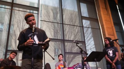 Talking Drum member, Marcelese Cooper, reads a poem about growing up as a black man in America for faculty and staff at a CitizenshipToo event.