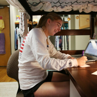 A student is studying in her residence hall.