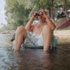 man sitting in shallow water, looking through binoculars