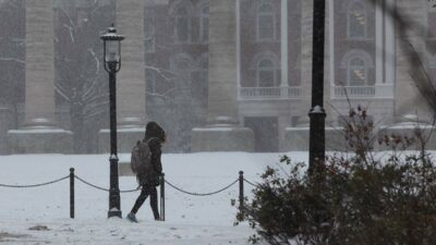 Student walks across snowy quad