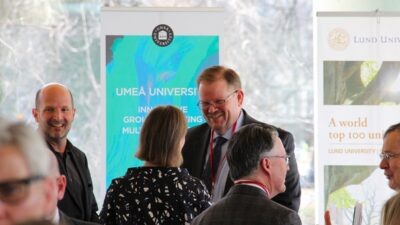 Chancellor Alexander Cartwright smiles as he speaks with a conference attendee.