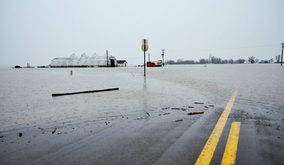 A county road disappears under receding floodwaters near Craig, Missouri.
