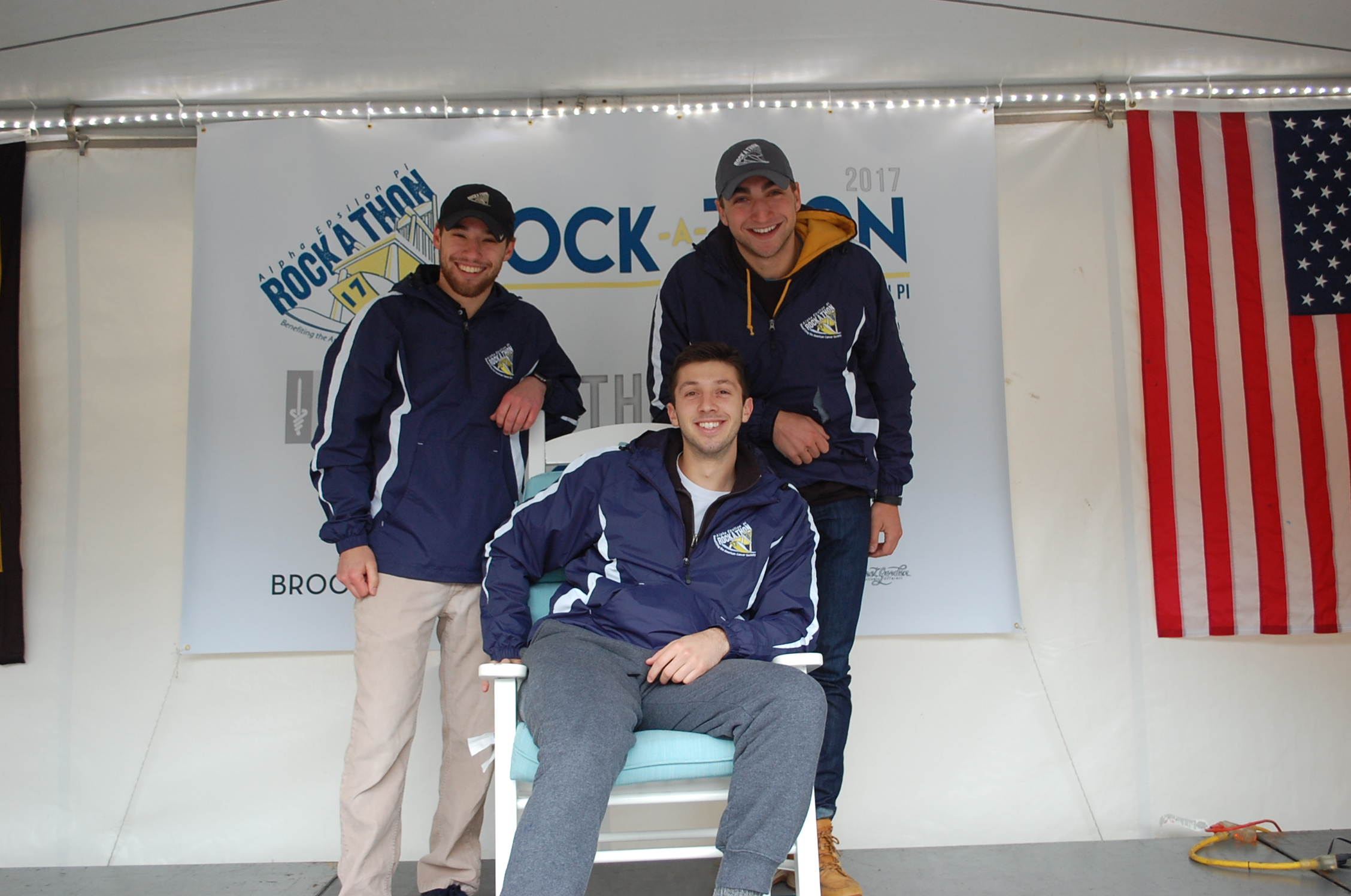 2017 Rock-A-Thon rocker Adam Bodner (sitting) is joined by co-chair Austin Dubinsky (left standing) and co-chair Adam Pressler (right standing). The Alpha Epsilon Pi chapter at MU has hosted the philanthropy every other April since 1969.