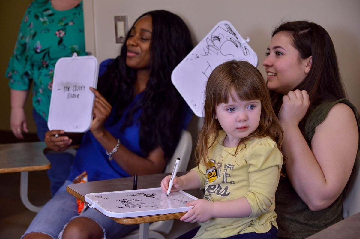 Two women and a young child participate in a whiteboard activity during Show Me Mizzou Day.
