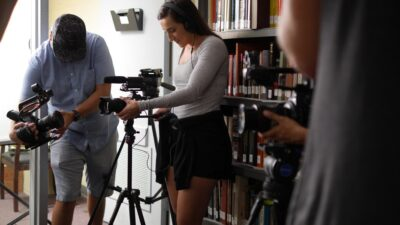 A picture of Taylor Hensel and her documentary team filming in a library.