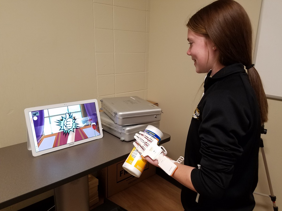 A middle school student uses the Rapael Smart Glove to replicate range of motion and therapy tasks used by occupational therapists and researchers treat patients and study various forms of therapy.