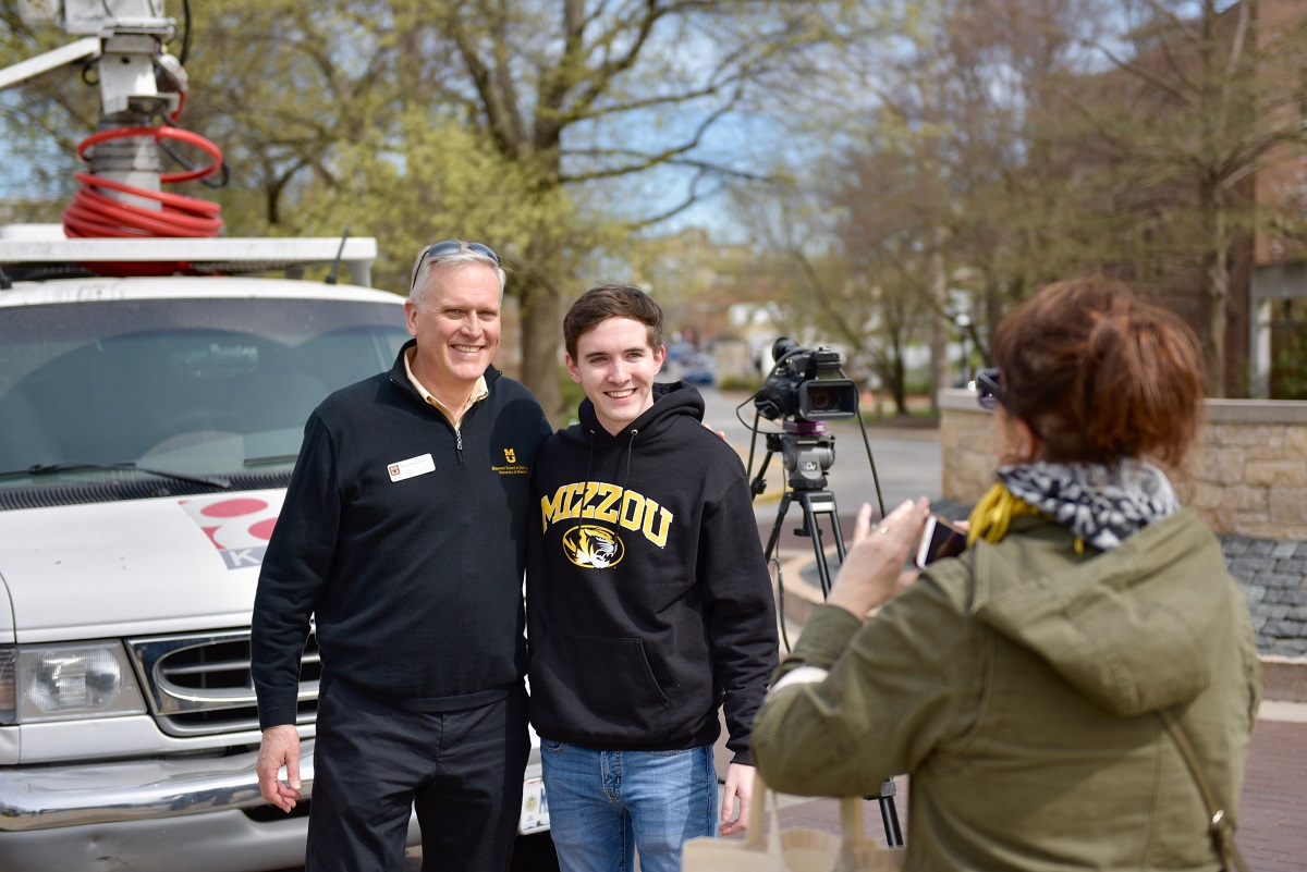 Matt McCabe, 18, of Overland Park, Kansas, poses for a photo with Dean David Kurpius outside the KOMU 8 live truck on the South Eighth Street circle. His mom, Susan, right, took the photo after the McCabe family visited the truck.