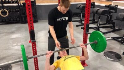Schmidt coaching an individual during a bench press