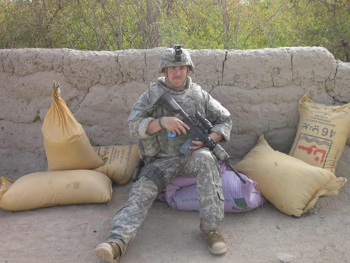 Alex Pracht, dressed in a military uniform and holding a weapon, sitting on the ground in front of wall.
