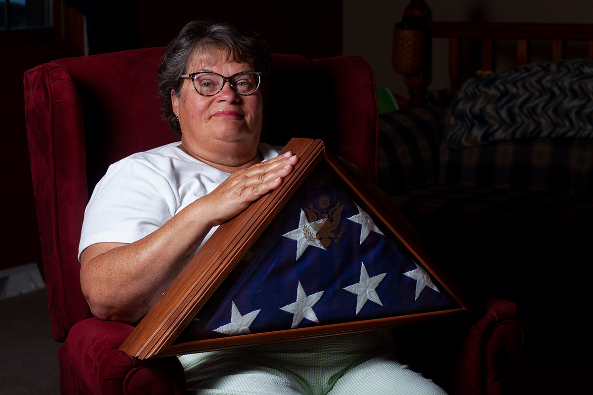 Nancy Jones sits holding her husband's military burial flag. She has a proud smile on her face.