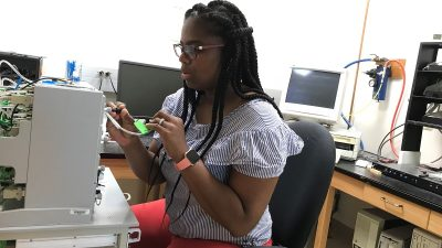 Patricka Williams-Simon, a doctoral fellow in biological sciences at MU who led the study, places fruit flies into a box to study how well they learn and remember. She and the team discovered some fruit flies learn better than others.