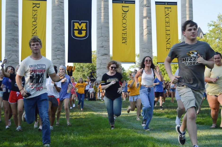 A photo of students running through the columns.